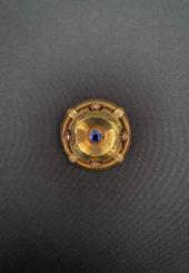 Broche « bouclier » en or jaune 18k ajourée ornée d'une pierre fine bleue